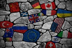 Wall consisting of stones painted in different flags of the world. Close-up royalty free stock photos