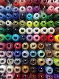 Wall of cotton reels, lots of colorful spools of thread displayed at the notions store, many sewing accessories for art and crafts. Background, haberdashery royalty free stock photo