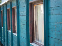 The wall of the country house. Picture of the wooden wall painted with turquoise blue colour. Old paintwork on the wall. An old country house made of planking royalty free stock photography