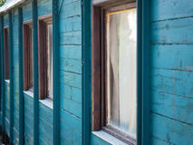 The wall of the country house. Picture of the wooden wall painted with turquoise blue colour. Old paintwork on the wall. An old country house made of planking royalty free stock photo