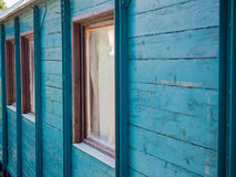 The wall of the country house. Picture of the wooden wall painted with turquoise blue colour. Old paintwork on the wall. An old country house made of planking royalty free stock photos