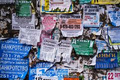 The wall is covered with old ads. VORONEZH, RUSSIA - MAR 25, 2019: The wall is covered with old ads. At the moment city was on the 14th place among the cities stock photography