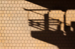 Wall covered with tiles and shadow. Wall covered with squared orange tiles with the shadow of a terrace on it. Picture taken in Italy where these styles were Royalty Free Stock Image