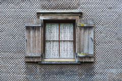 The wall covered with wooden shingles . The wall covered with wooden shingles and window Stock Photography