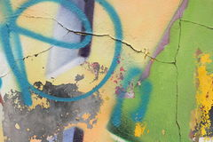 Wall with cracked plaster and peeling graffiti. Close-up view of a colorful peeling graffiti on a plastered wall with cracks royalty free stock photography