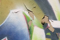 Wall with cracked plaster and peeling graffiti. Close-up view of a colorful peeling graffiti on a plastered wall with cracks royalty free stock photos
