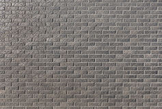 Wall from a dark brick with a pattern in a bright sunny day as a Royalty Free Stock Images