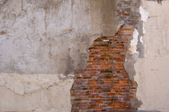 Wall decay texture. Damaged wall with bricks showing through plaster surface Royalty Free Stock Photo