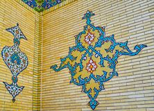 The wall decor of the portal of Malek museum, Tehran, Iran. The colorful tile arabesque on the brick wall of the portal of Malek museum, Bagh-e Melli quarter stock images