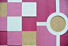 Wall decorated with pink and white wooden geometric designs. The wall decorated with pink and white wooden geometric designs stock photo