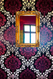 Wall decoration. Mirror with antique picture frame on a wall with purple wallpapers stock photo