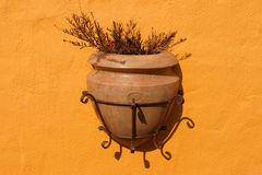 Wall decoration. Large decorative flowerpot attached to an orange painted wall royalty free stock image