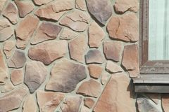Texture - artificial decorative stone façade. Decorative grey color rough stone wall background texture. Wall of decorative brick. Artificial stone stock images