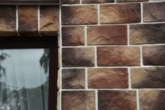 Texture - artificial decorative stone façade. Decorative grey color rough stone wall background texture. Stock Photography