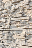 Wall of decorative stone sand color. Shallow depth of field, abstract background. Royalty Free Stock Photography