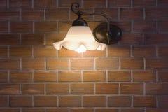 Wall desk lamp shining on brick stone wall. Royalty Free Stock Photo