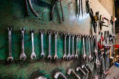 Wall with different metal instruments in little factory room Stock Photo