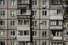 The wall of a dilapidated apartment building. Windows and balconies of a dilapidated house made of concrete. Several floors, many apartments. Bad living Stock Photography