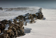 The wall. A dry stone wall at the edge of a field with snow blowing against it stock images
