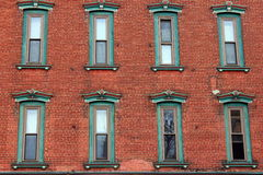 A wall of eight windows. Pretty old and weathered red brick wall with eight ornate windows adorning it royalty free stock photo