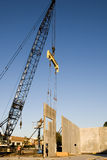Wall Erection. A crane setting a poured concrete two story wall in place stock photos