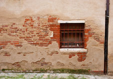 Wall with exposed brick and window with bars. Brick wall and window, Venice, Italy Stock Photos