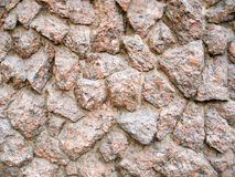 The wall faced with chunks of pink granite Stock Images