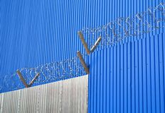 The wall and the fence of corrugated. Walls and fences of gray and blue corrugated wire with spikes royalty free stock image