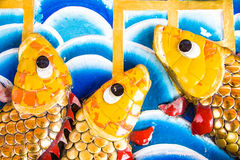 Wall with fish. Three fish yellow on the wall with the wall as a watermark royalty free stock photos