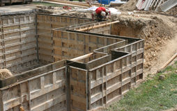 Wall forms / molds for concrete. A construction worker checking the measurements of steel forms set up making a mold, ready for concrete to be poured for the stock photography