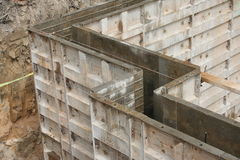 Wall forms / molds for concrete. Steel forms set up making a mold, ready for concrete to be poured for the walls of a basement room, seen in the dirt excavation Stock Photography