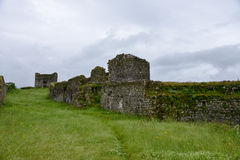 Wall of the Fort Lesendro, Montenegro. The wall of the fortress Lesendro with footpath in the grass in the foreground at the gloomy morning Royalty Free Stock Image