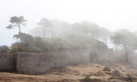 Wall of a fortress on the hillside. Covered fog Royalty Free Stock Images