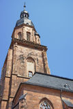 Wall fragment and spire of Cathedral of Holy Spirit in Heidelber. Wall fragment, clock tower and spire of Cathedral of Holy Spirit in Heidelberg at sunny weather Royalty Free Stock Photo