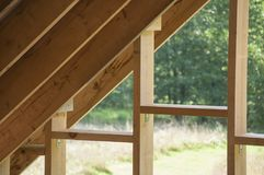 Wall frame on log house attic and rafters of roof construction. Wall frame on log house attic and the rafters of roof construction stock images