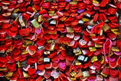 Wall full of red and pink love locks shaped as hearts and classical locks with writings on each lock, in Verona stock images