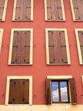 Wall full of Windows, one open. To the sky Royalty Free Stock Photo