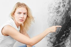 Free Wall Fungus. Aspergillus. A Beautiful Girl In A White T-shirt Points A Finger At The Black Mold On The Wall Royalty Free Stock Photos - 140297508