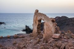 Wall with gate of a building demolished on a cliff facing the sea stock photos