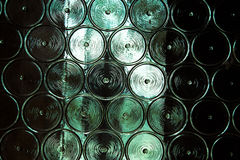 Wall of glass bottles with somthing metall behind it. Selective Stock Photo