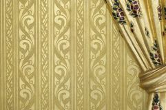 Golden royal Thai wall decoration art. A wall with golden looked royal Thai art and pattern. Its right side is a curtain-like sculpture Royalty Free Stock Image