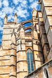 Wall Gothic cathedral in Palma de Mallorca on the sky background. Bottom view on the wall of a Gothic cathedral on the sky background in Palma de Mallorca in the Stock Image