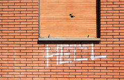 Wall with graffiti. Brick wall with the word hell written with spray Royalty Free Stock Image