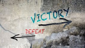 Wall Graffiti Victory versus Defeat. Wall Graffiti the Direction Way to Victory versus Defeat stock images