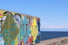 Wall with graffiti and the sea. Stock Photos