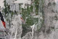 Wall with Graffiti and torn posters. A concrete wall with fragments of black, red and white torn posters and green wall color royalty free stock photo