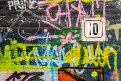A wall with graffiti of unknown artists. Number of the house on the wall. Street art. Copyspace for text and design Royalty Free Stock Image