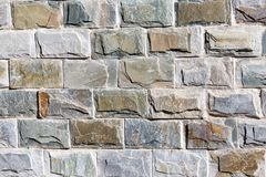 Wall of granite bricks as background stock images