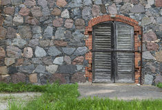 Wall from granite stones with a door and  the old asphalt road o Stock Photography