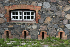 Wall from granite stones with a window and  the old  road overgr Royalty Free Stock Photos